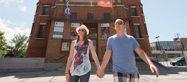 Happy couple holding hands while leaving the Orillia Opera House